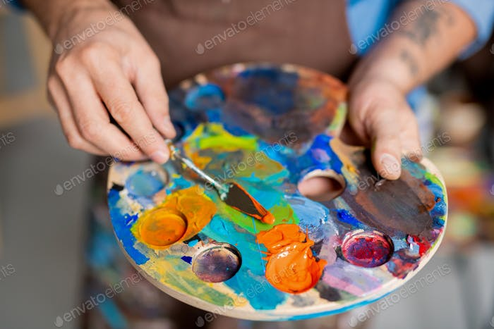Hand of painter mixing paints on palette with small instrument before painting