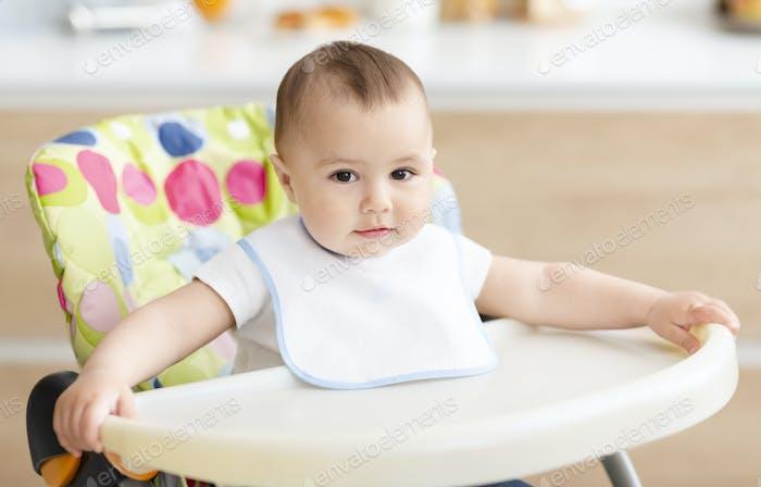 Cute baby boy sitting in high children chair in kitchen