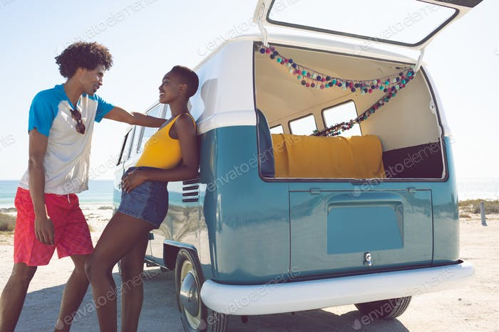 Happy African american couple talking with each other near camper van at beach in the sunshine