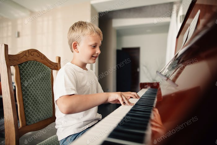 little happy boy plays piano