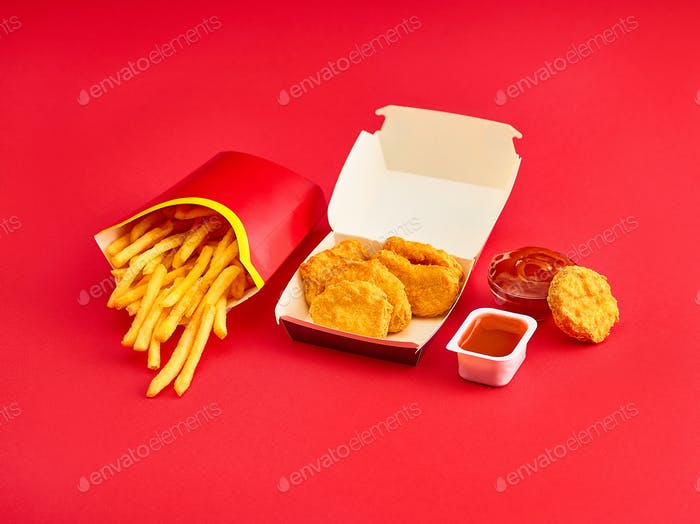 chicken nuggets and french fries on red background