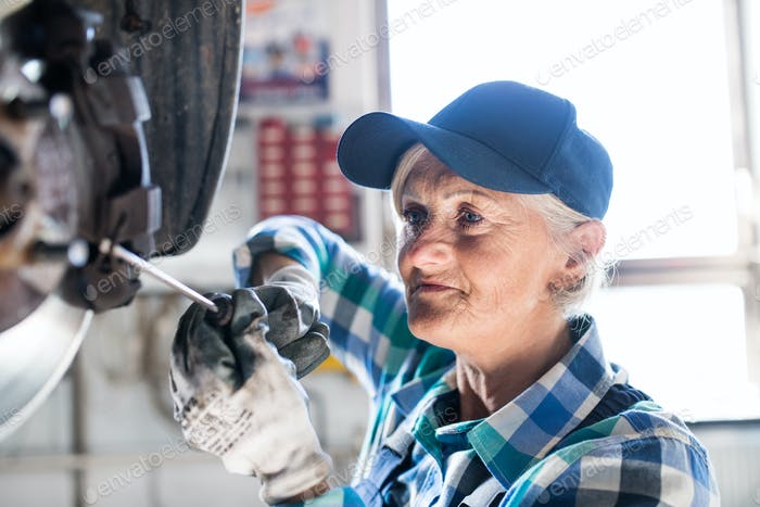 Senior female mechanic repairing a car in a garage.