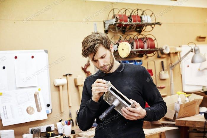 Eine Möbelwerkstatt. Ein junger Mann hält ein Objekt und untersucht es genau.