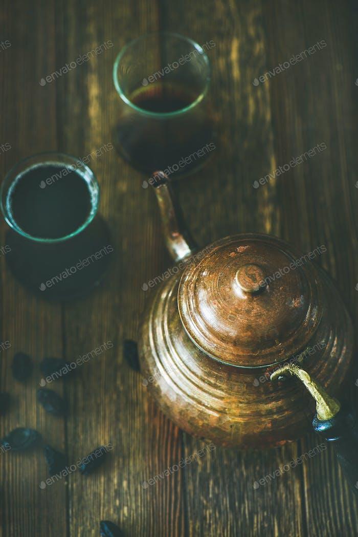 Oriental tea pot, black tea in tulip glasses and raisins