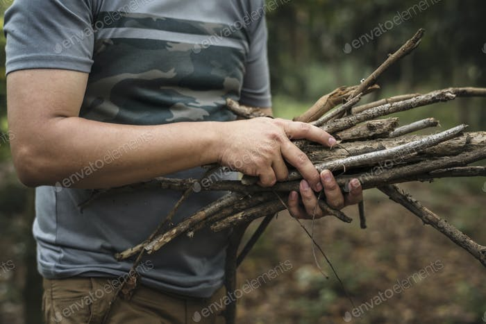 Man collecting dry twigs for bonfire