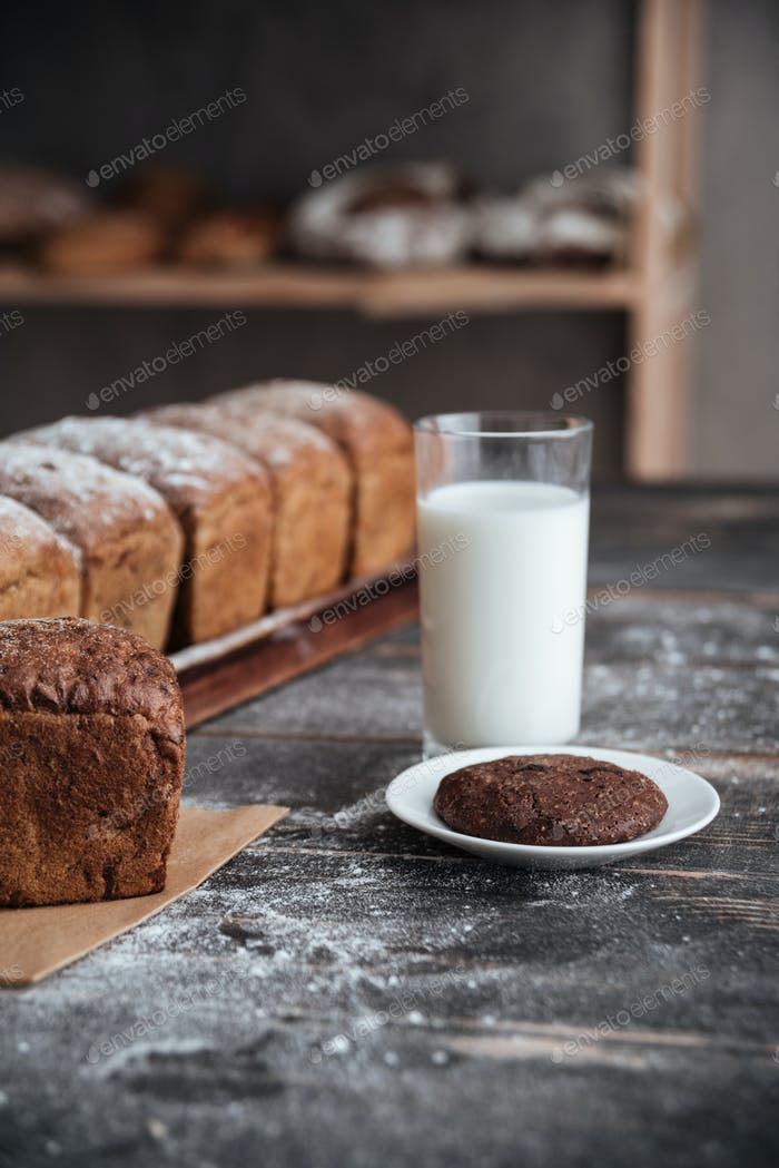 Bread with flour on wooden table with milk and cookie