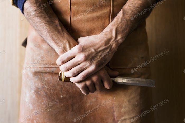 Midsection of carpenter holding chisel in workshop