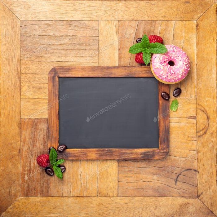 Black chalkboard with pink glazed donut