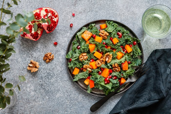 Top view on a vegetarian salad which is made from raw vegetables such a persimmon, kale