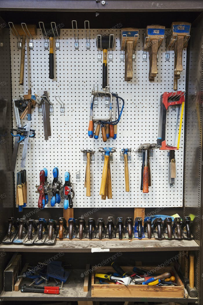 Work bench in a boat-builder's workshop, selection of hand tools for wood working hanging on a wall.