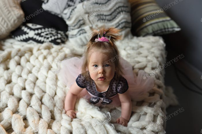 A little girl with a hairpin on her head lies on her stomach on the bed and looks into the frame.