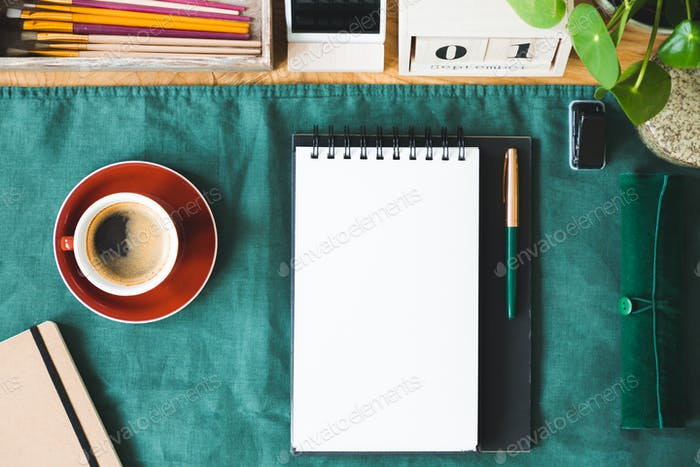 Top view on red cup of coffee and notes with copy space on green