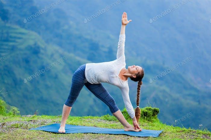 Woman doing Ashtanga Vinyasa yoga asana Utthita trikonasana
