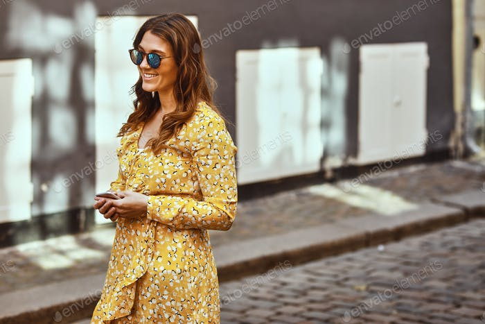 Smiling young woman walking in the city holding a cellphone