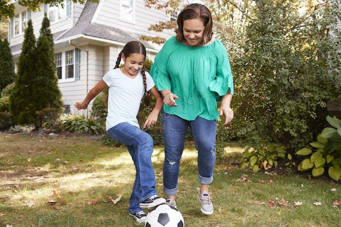 Großmutter spielen Fußball in Garten mit Enkelin