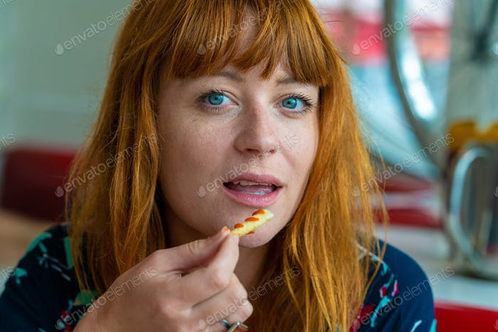 Portrait of ginger girl with blue eyes on a floral dress in a eating chips and smiling