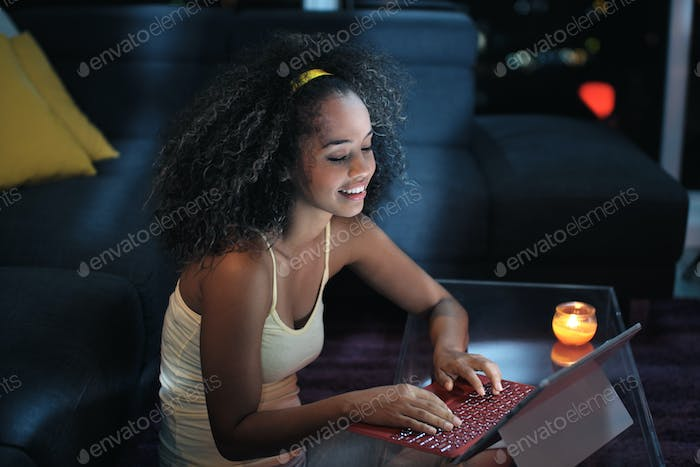 Young Latina Woman Typing Message on Laptop At Night