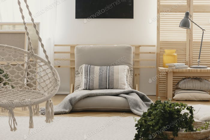 Pillow and blanket on grey futon in boho bedroom interior with l
