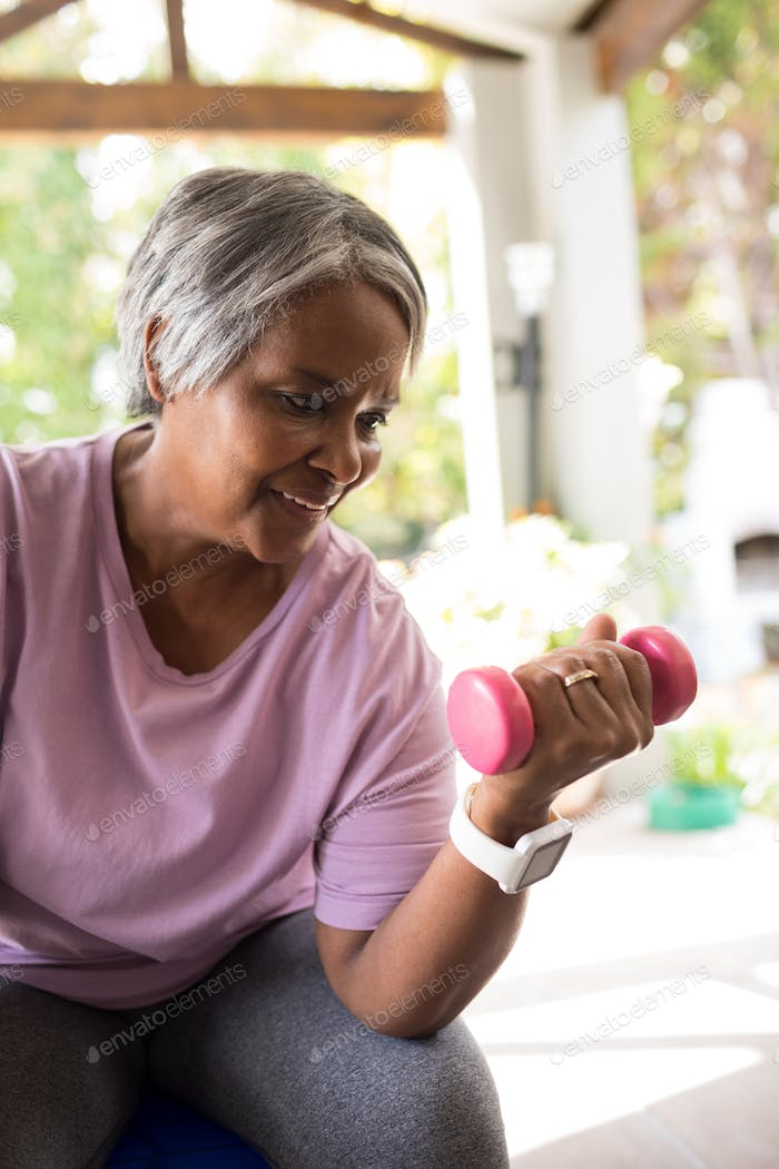 Close up of smiling senior woman exercising with dumbbell