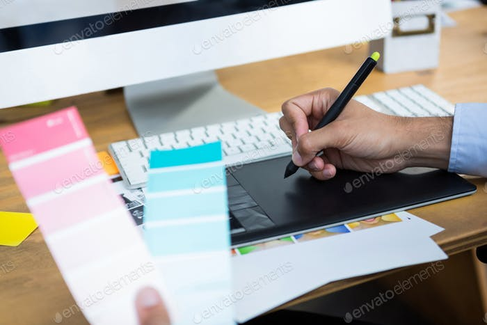 Close-up of female graphic designer working at desk