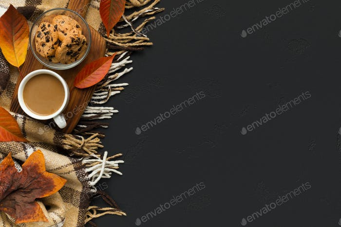 Coffee with biscuit on background with scarf and fallen leaves