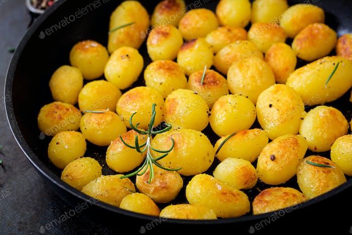 Gebackene Kartoffeln mit Rosmarin und Pfeffer in einer Pfanne auf schwarzem Hintergrund