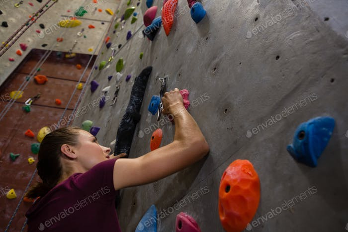Low angle view female athlete climbing wall