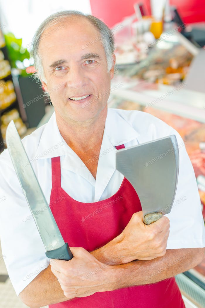 Butcher holding knife and cleaver, arms crossed
