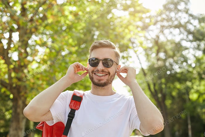 Close-up of happy hipster walking through park on sunny day, wearing sunglasses and white t-shir