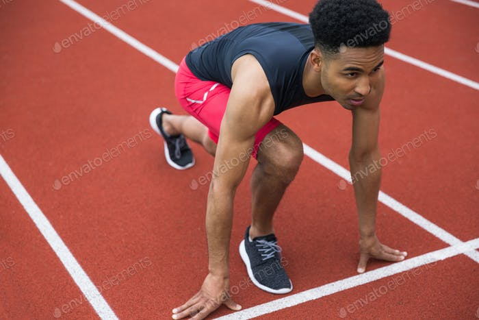 Handsome concentrated african athlete man ready to start