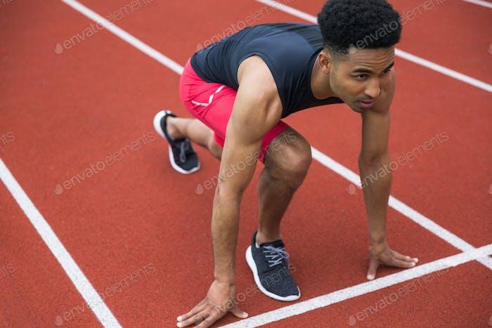 Schöner konzentrierter afrikanischer Athlet Mann bereit zu starten
