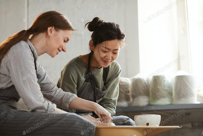 Содержание многоэтнических женщин, создавая глиняный горшок вместе