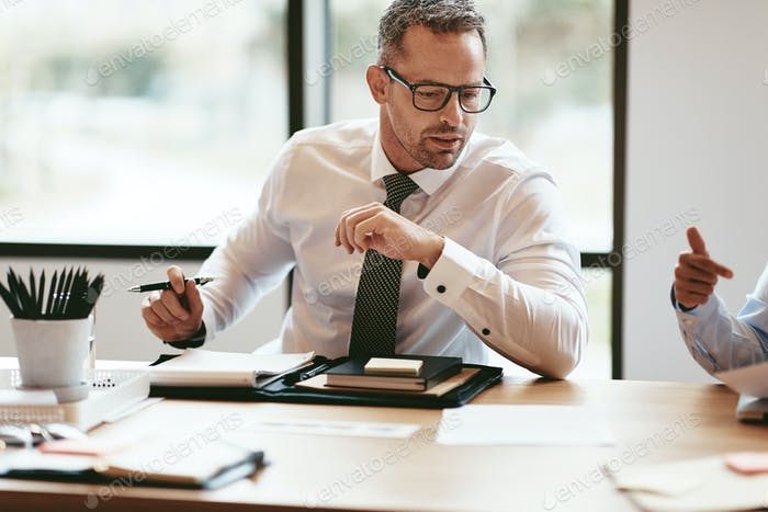 Mature businessman going over paperwork during a boardroom meeting