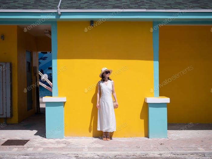 Attraktives Mädchen an der gelben Wand
