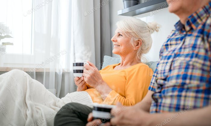 Senior couple at home spending time together drinking tea or coffee