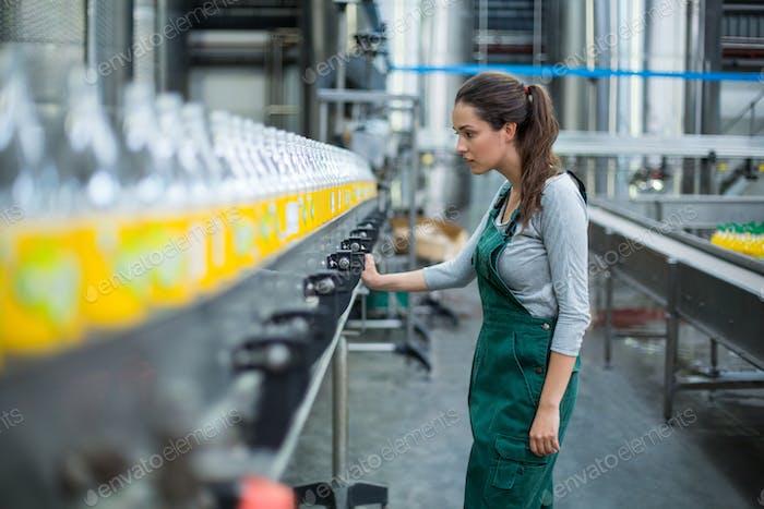 Weibliche Fabrikarbeiterin steht in der Nähe der Produktionslinie