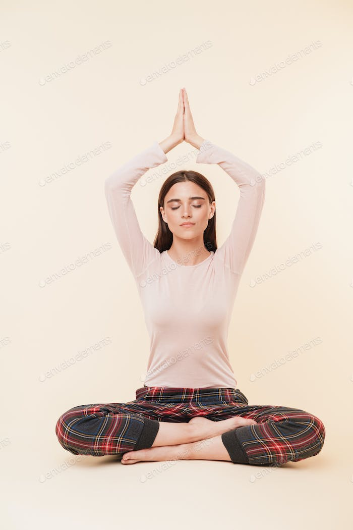 Calm young brunette girl meditating while sitting