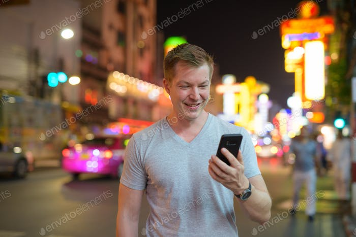 Young happy tourist man using phone in the streets of Chinatown at night
