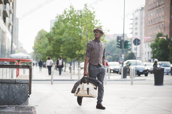 Young handsome afro black man walking in the street of the city,