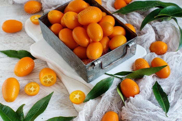 Kumquat fruits on a grey background