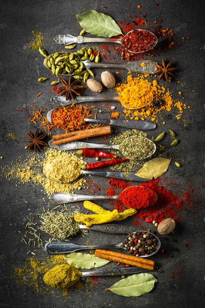Spices in spoons on black background.