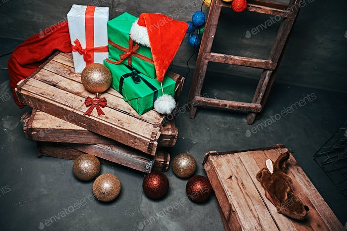 Gift boxes, tree balls, hat and bag with vintage wooden boxes and ladder.
