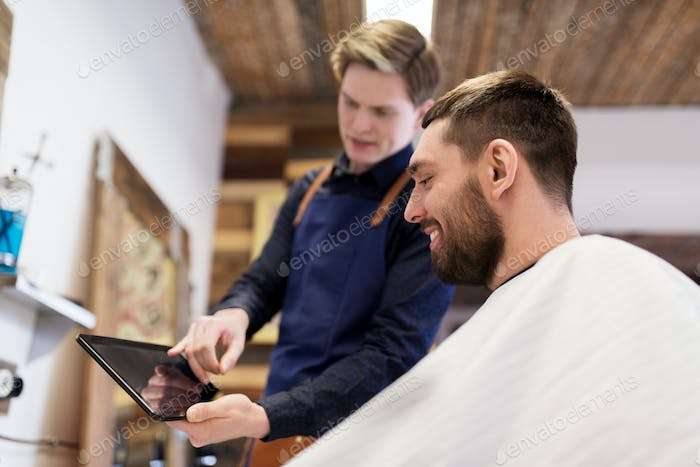 barber showing tablet pc to man at barbershop