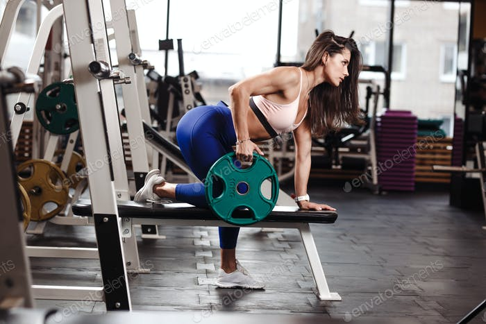 Young athletic brunette girl dressed in a sportswear is doing exercises with plate on the bench in