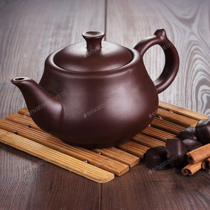 Teekanne mit heißem Tee und Zimtstangen
