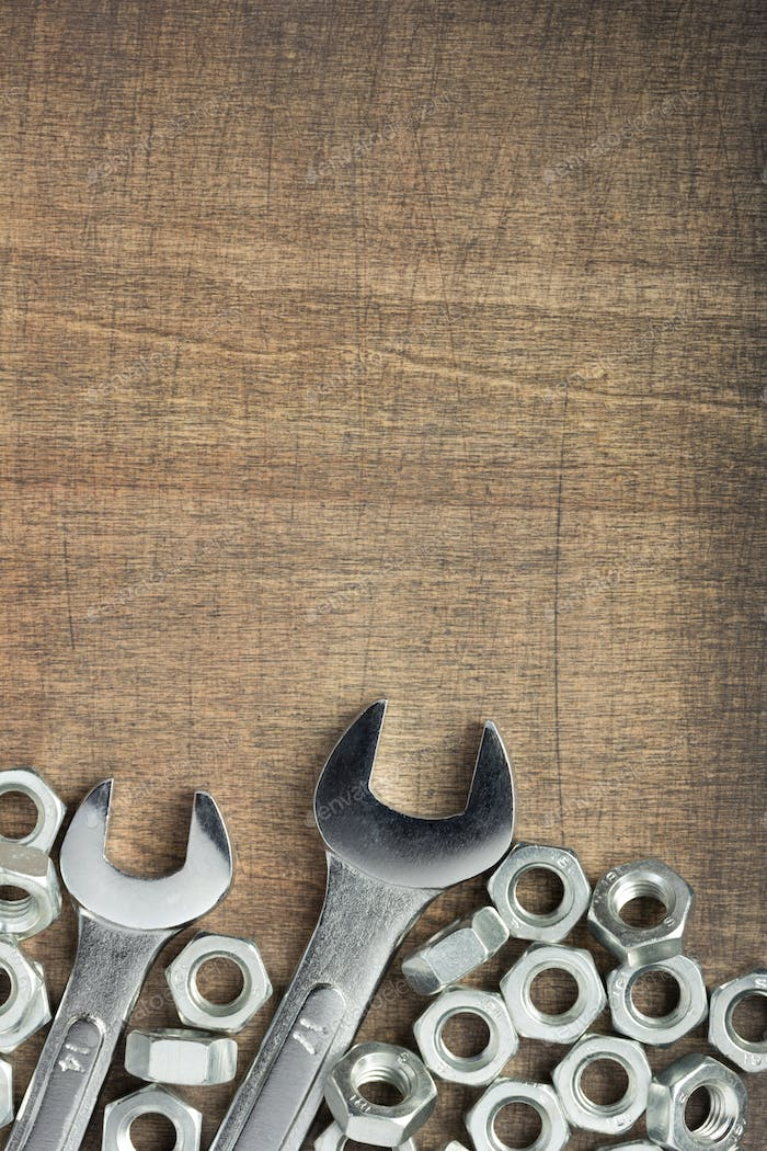 wrench tools and metal nuts at wood