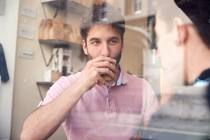 Male Gay Couple Sitting Inside Coffee Shop On Date Viewed Through Window