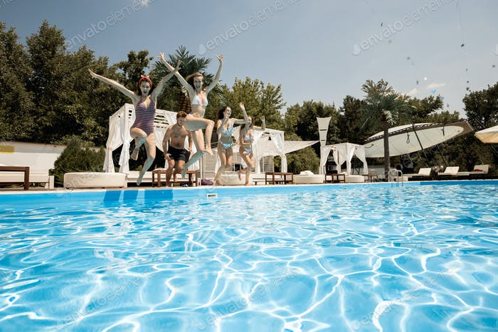 Company of young merry girls and guy jump together in the swimming pool next to lounge zone on the