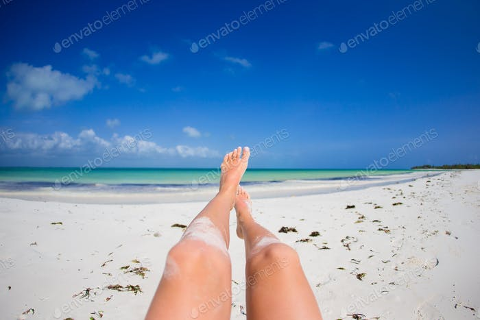 Female feet on white sandy beach