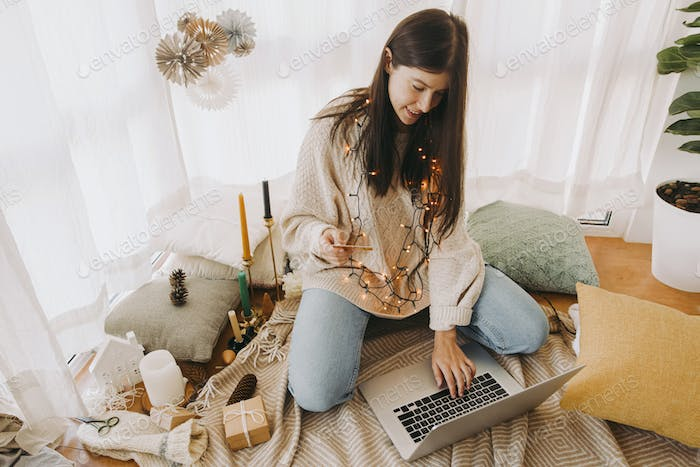 Happy young woman shopping online using laptop and credit card. Christmas and Black Friday sale